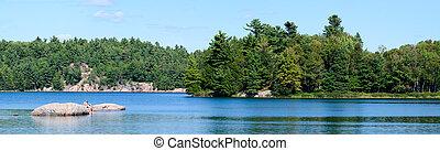 Family on rocky island on a blue lake