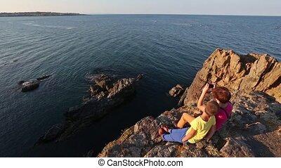 Family on Rocky Sea Coast.