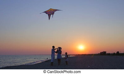 Family on sandy beach flying kite in the sky at sunset