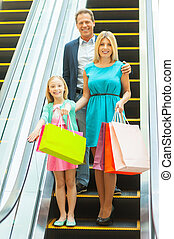 Family on shopping spree. Cheerful family holding shopping bags and smiling at camera while moving by escalator