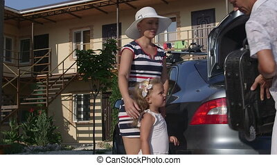 Family on summer vacation arriving at hotel father taking off suitcase from car