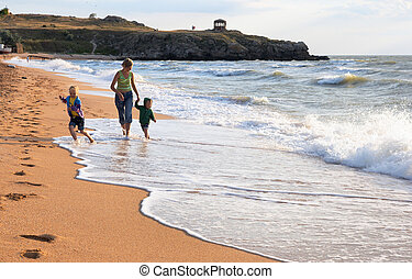 Family on surf beach - Walking family on sandy beach and...