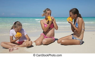 family on the beach eating mango fruit