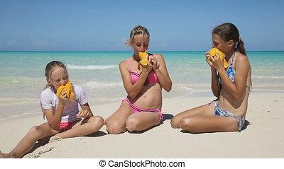 family on the beach eating mango fruit