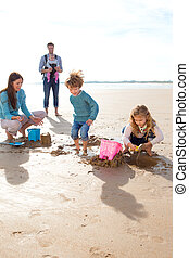 Family on the Beach - Family of five splashing and digging...