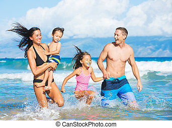 Happy Mixed Race Family of Four Playing and Having Fun on the Beach