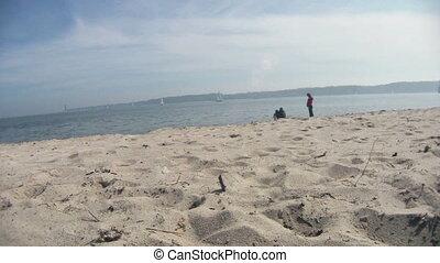 Family on the beach with cargo ship