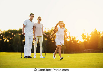 Family on the golf course, happy girl running across the field, her parents are standing with golf clubs behind