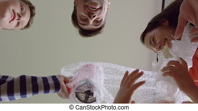 Family opening cardboard box at new home 4k - Upward view of...
