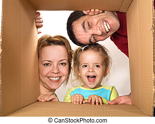 Family opening cardboard box - happy moving concept - Happy...