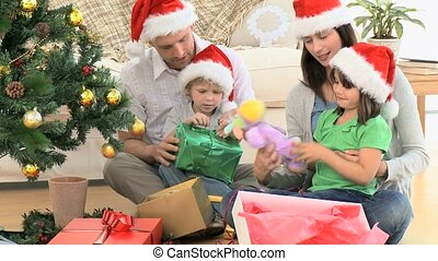 Lovely family opening Christmas gifts while sitting on the floor in the living-room