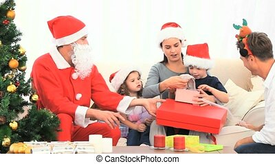 Family opening Christmas gifts with Santa Claus