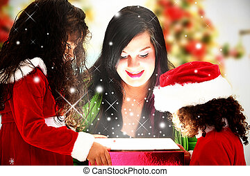 Family Opening Magical Christmas Present - Mother and...