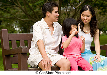 Family Outdoors - A young couple with a small child spending...