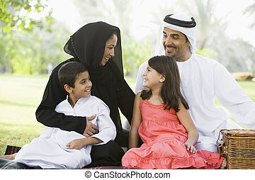 Family outdoors in park having a picnic and smiling (...