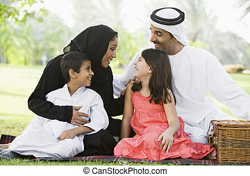 Family outdoors in park having a picnic and smiling (selective focus)