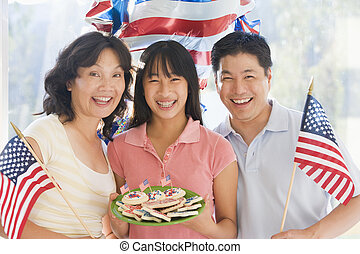 Family outdoors on fourth of July with flags and cookies...