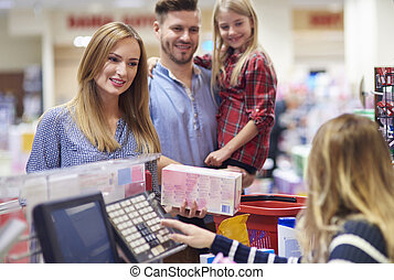 Family packing shopping at supermarket checkout