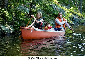 family paddeling a canoe on a wilderness lake