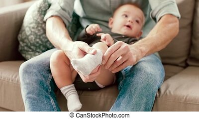 father putting sock on baby daughters foot - family,...