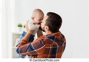 happy father kissing little baby boy at home