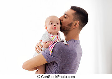 father kissing little baby daughter