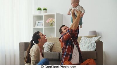 happy mother and father playing with baby at home