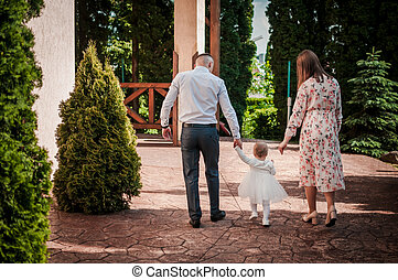 Family, parents walk with their daughter