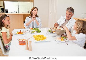 Family passing around breadbasket during dinner