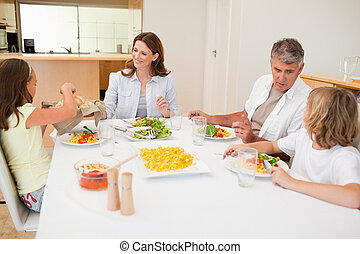 Family passing around the breadbasket during dinner