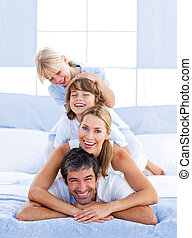 Family piled on top of dad in the bedroom