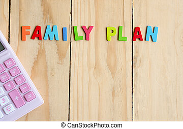 Family planning text with pink calculator on wood table background