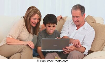 Family playing a game on a laptop in the living room