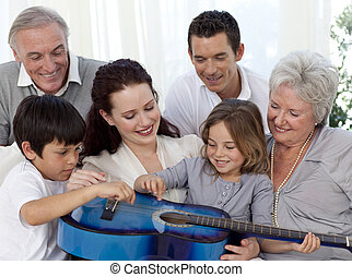 Family playing a guitar in living-room