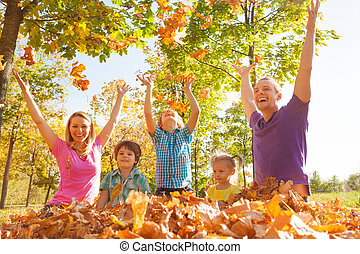 Family playing and throwing leaves in the air