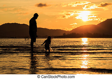 Family playing at beach in sunset time