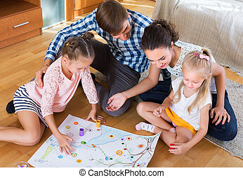 Family playing at board game - Happy young family of four ...