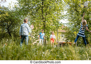 Family playing badminton on a meadow in summer
