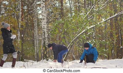 family playing by throwing snowballs in the winter Park