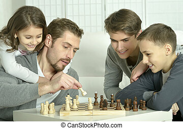 Family playing chess at home