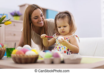 Family playing during painting easter eggs