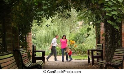 family playing game in plant tunnel of park - Happy family...