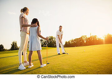Family playing golf at sunset. A woman and a girl are looking at a man who is preparing to make a hit