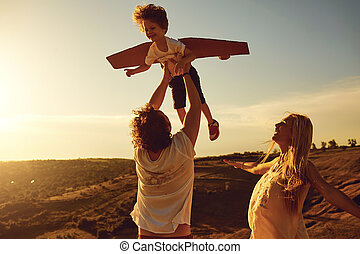Family playing in nature at sunset