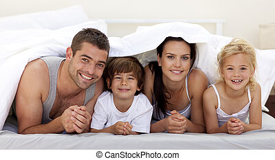 Happy young family playing in parent's bed