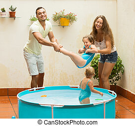 Family playing in pool at terrace - Positive joyful young...