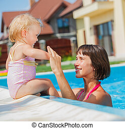 Family playing in swimming pool.