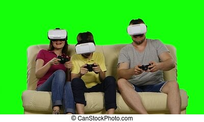 Family playing in the game of virtual masks sitting on the sofa. Green screen