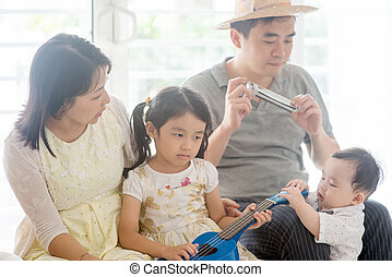 Family playing music instrument at home