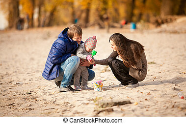 Family playing on beach with daughter at autumn